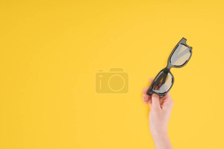 cropped view of female hand holding stereoscopic 3d glasses isolated on yellow