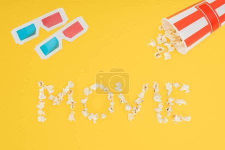 "3d glasses, overturned striped bucket and ""movie"" lettering made with popcorn  isolated on yellow"