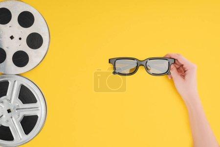 Photo pour Bobines de film et de la femelle main tenant des lunettes 3d stéréoscopiques isolés jaune - image libre de droit