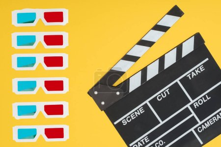 Photo for 3d glasses in vertical row and clapperboard isolated on yellow - Royalty Free Image