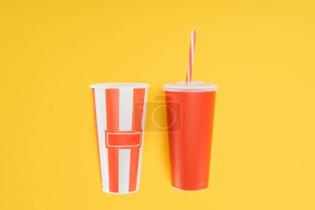 striped popcorn bucket and red disposable cup with straw isolated on yellow