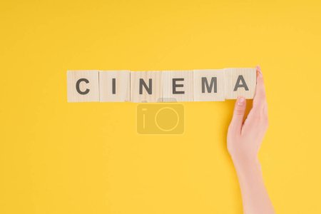 "top view of female hand touching wooden cubes with ""cinema"" lettering isolated on yellow"