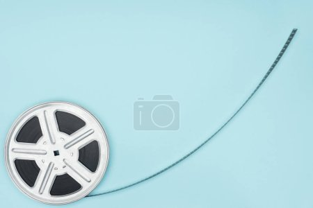 movie reel with cinema tape isolated on blue