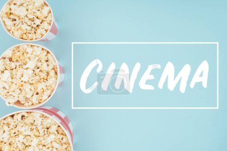 "top view of buckets with popcorn in vertical row and ""cinema"" lettering isolated on blue"