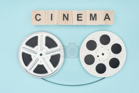 "wooden cubes with ""cinema"" lettering and film reels with cinema tape between them isolated on blue"