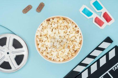 Draufsicht auf Klappbrett, Filmspule, 3D-Brille, Kinokarten und Popcorn-Eimer isoliert auf blau