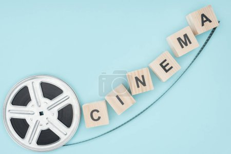 "wooden cubes with ""cinema"" lettering and movie reel isolated on blue"