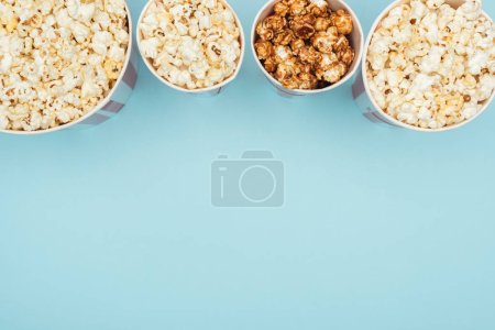 top view of buckets with popcorn in horizontal row isolated on blue