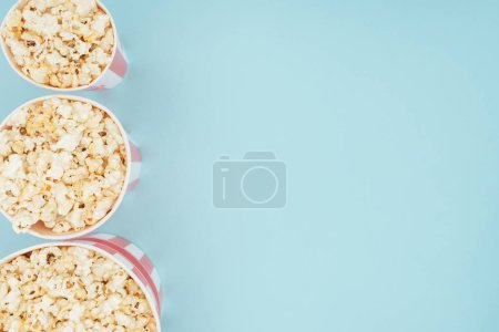 Photo for Top view of buckets with popcorn in vertical row isolated on blue - Royalty Free Image
