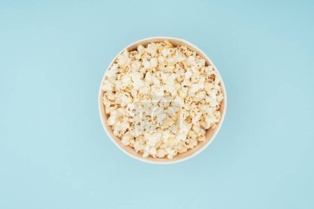 Photo for Top view of bucket with fresh tasty popcorn isolated on blue - Royalty Free Image