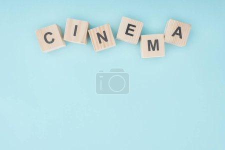 "wooden cubes with ""cinema"" lettering isolated on blue"