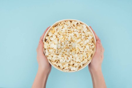 Photo for Top view of hands holding bucket with popcorn isolated on blue - Royalty Free Image