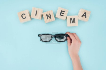"top view of wooden cubes with ""cinema"" lettering and hand holding 3d glasses isolated on blue"