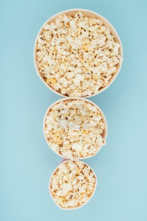 top view of popcorn buckets of different sizes in vertical row isolated on blue