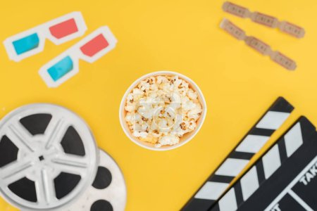 top view of clapperboard, film reels, 3d glasses, cinema tickets and popcorn bucket isolated on yellow