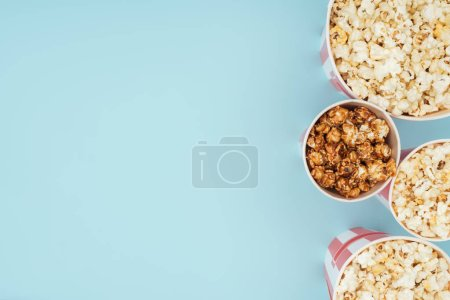 top view of buckets with popcorn in vertical row isolated on blue