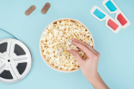 top view of film reel, 3d glasses, cinema tickets and hand taking popcorn from bucket isolated on blue