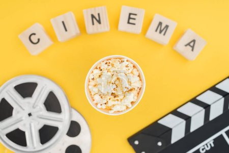 """top view of wooden cubes with """"cinema"""" lettering, clapperboard, film reels and popcorn bucket isolated on yellow"""