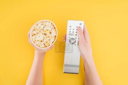 Photo pour Vue de dessus des mains tenant le seau de pop-corn et de la télécommande isolé jaune - image libre de droit