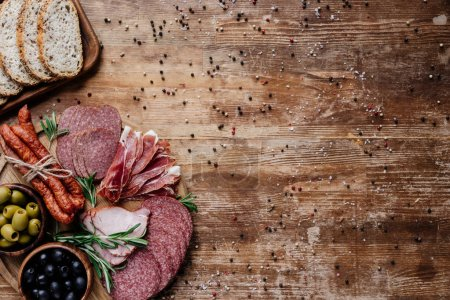 top view of cutting boards with delicious salami, smoked sausages, olives and bread on wooden table with scattered peppercorns