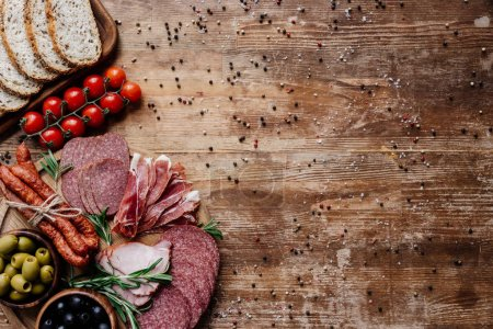 Photo for Top view of cutting boards with tasty salami, smoked sausages, olives, tomatoes and bread on wooden table with scattered peppercorns - Royalty Free Image