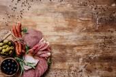 """Постер, картина, фотообои """"вид сверху круглых разделочная доска с вкусные колбасы, ветчины и оливки в мисках на деревянный стол с рассеянных пряностей"""""""