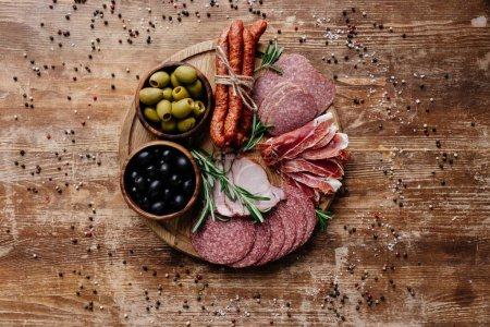 Photo for Top view of round cutting board with delicious salami, prosciutto and olives in two bowls on wooden table with scattered spices - Royalty Free Image