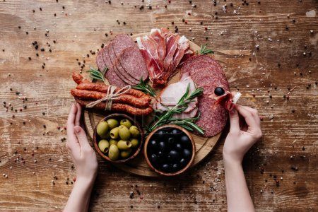 cropped view of  woman taking prosciutto from round cutting board with olives, salami and ham on wooden table with scattered peppercorns