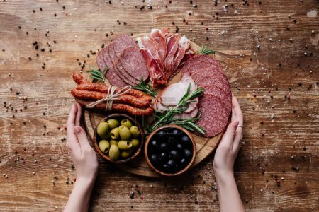 Photo for Top view of  female hands holding round cutting board with olives in two bowls and sliced salami, prosciutto and ham on wooden table with scattered peppercorns - Royalty Free Image