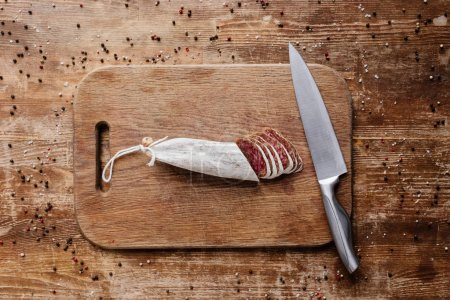 top view of cutting board with steel knife and tasty sliced salami on wooden table with scattered peppercorns