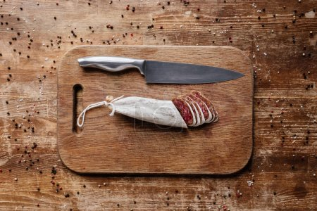 top view of wooden cutting board with steel knife and sliced salami on table with scattered spices