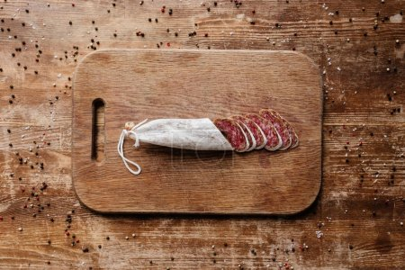 Photo for Top view of cutting board with delicious sliced salami on wooden table with scattered peppercorns - Royalty Free Image