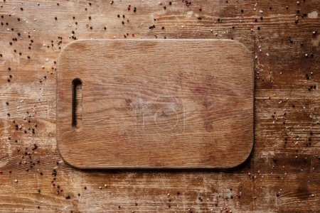 top view of cutting board on wooden table with scattered peppercorns