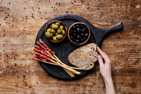 cropped view of  woman putting bread on round cutting board with olives, breadsticks and prosciutto on wooden table