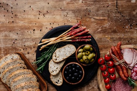 top view of cutting boards with olives, breadsticks, prosciutto, salami, bread, tomatoes and herbs on wooden table