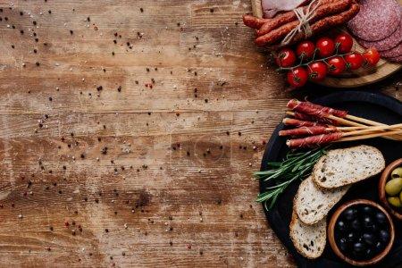 Photo pour Vue de dessus des planches à découper avec les olives dans les bols, gressins, prosciutto, saucisses fumées, saucisson, pain, tomates et fines herbes sur la table en bois - image libre de droit