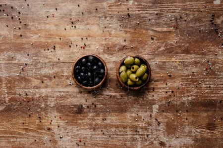 Photo for Top view of two bowls with black and green olives on wooden table with scattered peppercorns - Royalty Free Image
