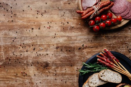 Photo for Top view of cutting boards with olives in bowls, delicious smoked sausages, salami, bread, tomatoes and herbs on wooden table with scattered spices - Royalty Free Image