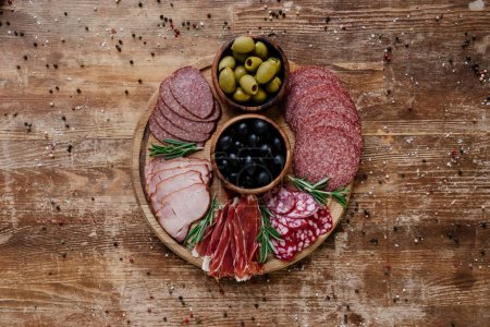 top view of round cutting board with olives and sliced salami, prosciutto and ham on wooden table with scattered spices