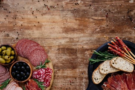 top view of cutting boards with olives, breadsticks, prosciutto, salami, bread and herbs on wooden table