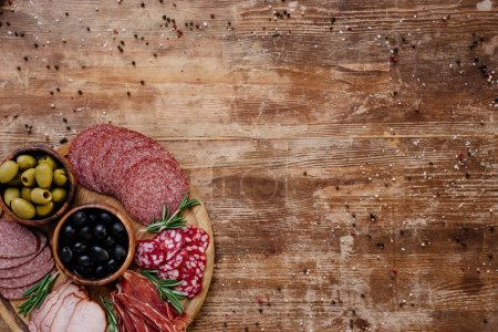 top view of cutting board with olives, breadsticks, delicious prosciutto, salami and herbs on wooden table with scattered spices