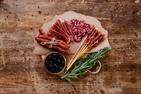 top view of round cutting board with black olives, delicious prosciutto, salami, smoked sausages and herbs on wooden vintage table with scattered peppercorns