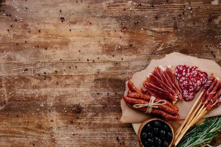 Photo for Top view of round cutting board with delicious prosciutto, salami, smoked sausages, olives and herbs on wooden vintage table with scattered peppercorns - Royalty Free Image