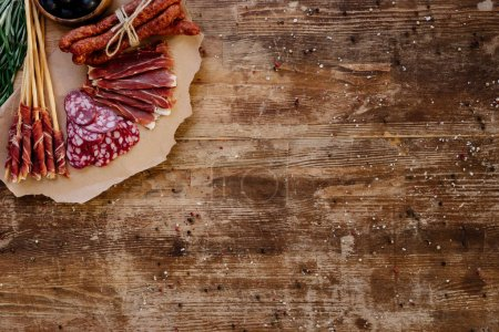 top view of cutting board with sliced prosciutto, salami and smoked sausages on wooden vintage table  with scattered spices