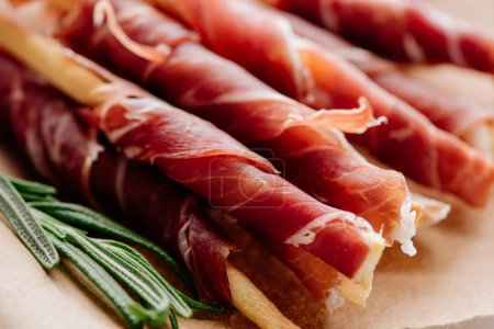 close up view of rosemary and delicious sliced prosciutto wrapped around breadsticks  on brown wrapping paper