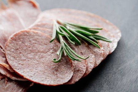 Photo for Close up view of little rosemary branch on delicious sliced salami - Royalty Free Image