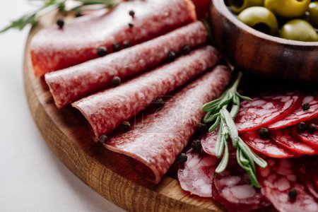 Photo for Close up view of delicious sliced salami with rosemary and peppercorns on wooden cutting board - Royalty Free Image