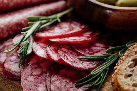 Photo for Close up view of delicious sliced salami with rosemary and bread on wooden cutting board - Royalty Free Image
