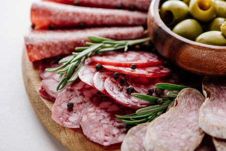 close up view of delicious sliced salami with spices and olives in bowl on wooden cutting board