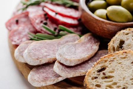 close up view of delicious sliced salami, bread and olives in bowl on wooden cutting board